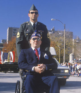 two veterans stood on the street one in a wheelchair